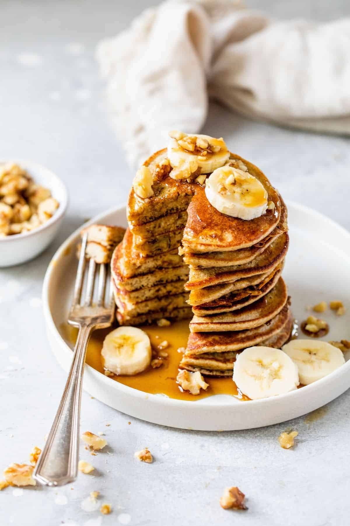 serving of banana oatmeal pancakes served with banana slices and chopped walnuts