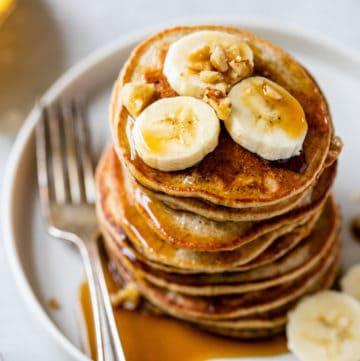 banana oatmeal pancakes with sliced bananas on top