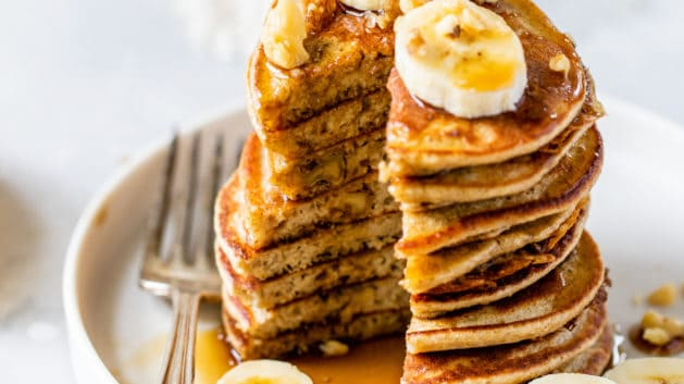 banana oatmeal pancakes cut into and topped with bananas