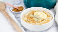 creamy bowl of oatmeal topped with banana and peanut butter
