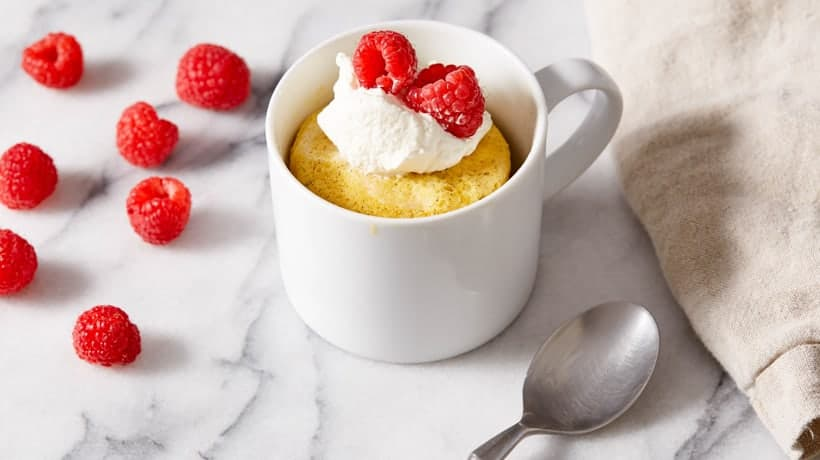 vanilla mug cake topped with whipped cream and berries