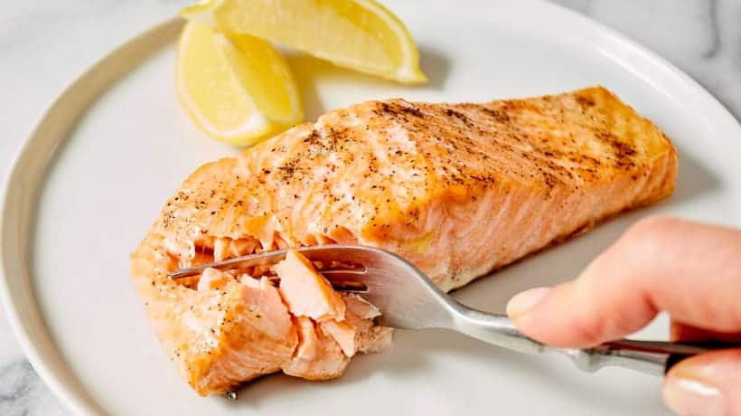 fork cutting into flaky salmon filet