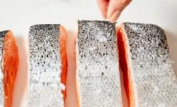 sprinkling salt on salmon skin