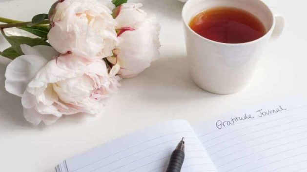 a journal, flowers, and tea on a desk
