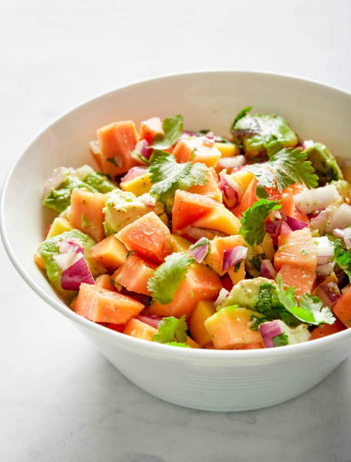 papaya salsa with avocado and cilantro in a white bowl