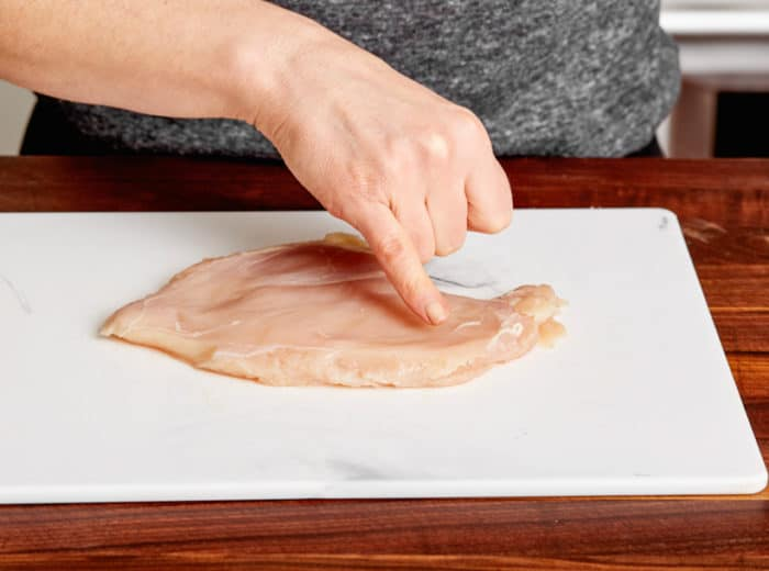 raw chicken pounded out evenly