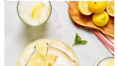 homemade lemonade in a pitcher near fresh lemons