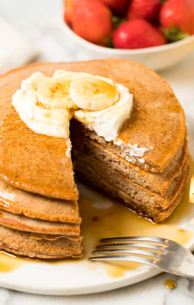 stack of pancakes topped with yogurt and banana on a white plate