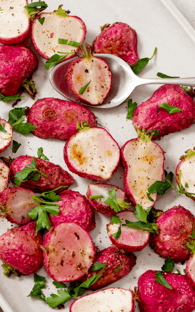 roasted radishes served on a white platter with fresh parsley