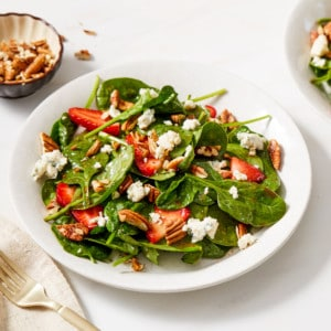 strawberry spinach salad in a white bowl