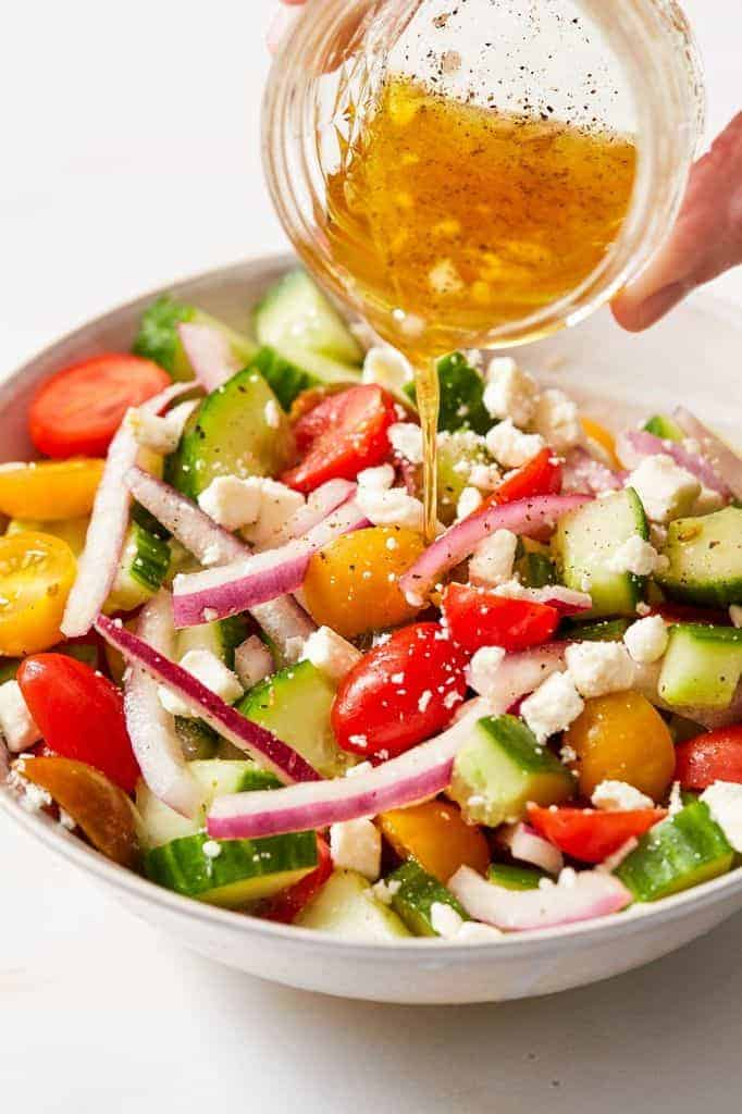 pouring vinaigrette over chopped veggie salad