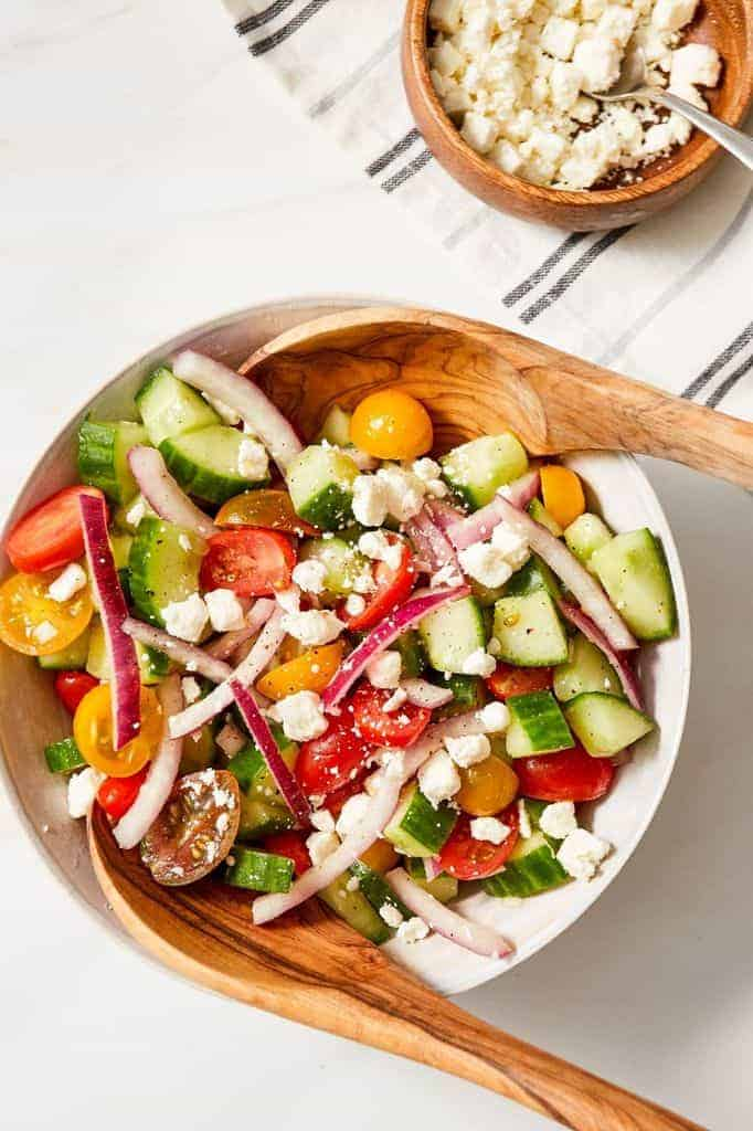 using salad tongs to toss a tomato cucumber onion salad
