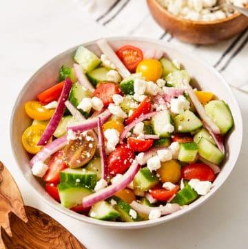 cucumber tomato onion salad in white bowl