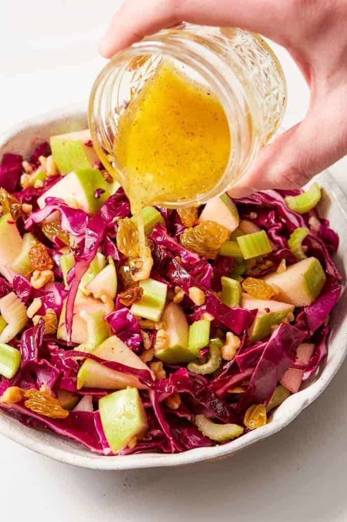 pouring lemon vinaigrette over red cabbage salad