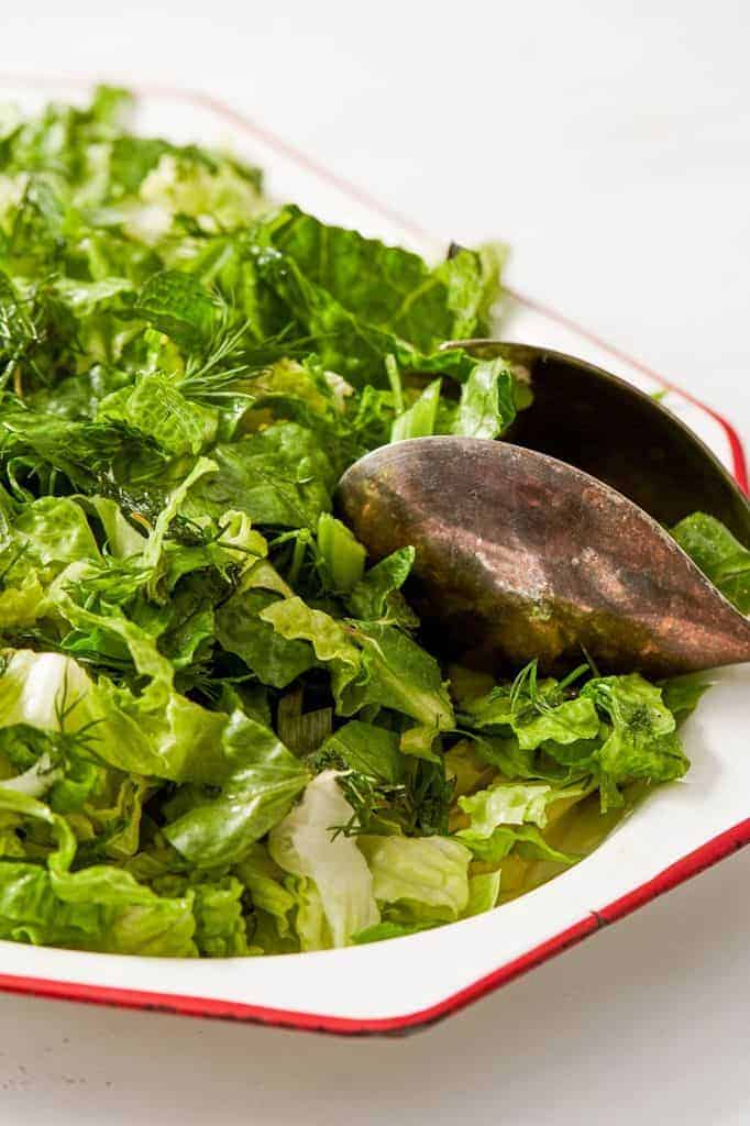 salad tongs in a romaine lettuce salad