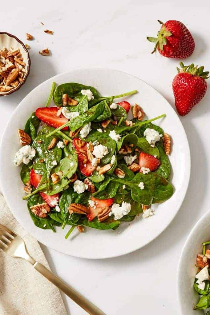 strawberry spinach salad served on a white plate