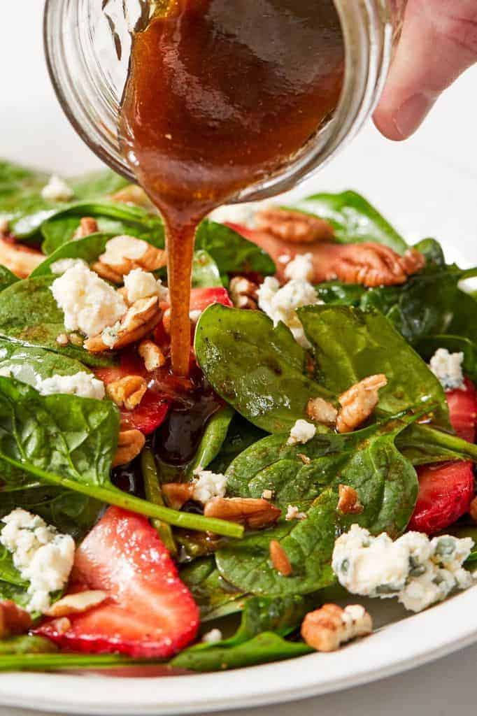 pouring balsamic vinaigrette over spinach salad