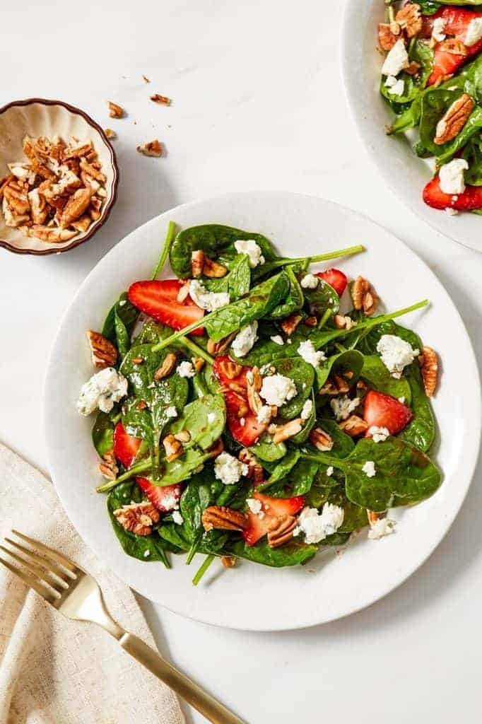 spinach salad topped with fresh strawberries, pecans and Gorgonzola cheese
