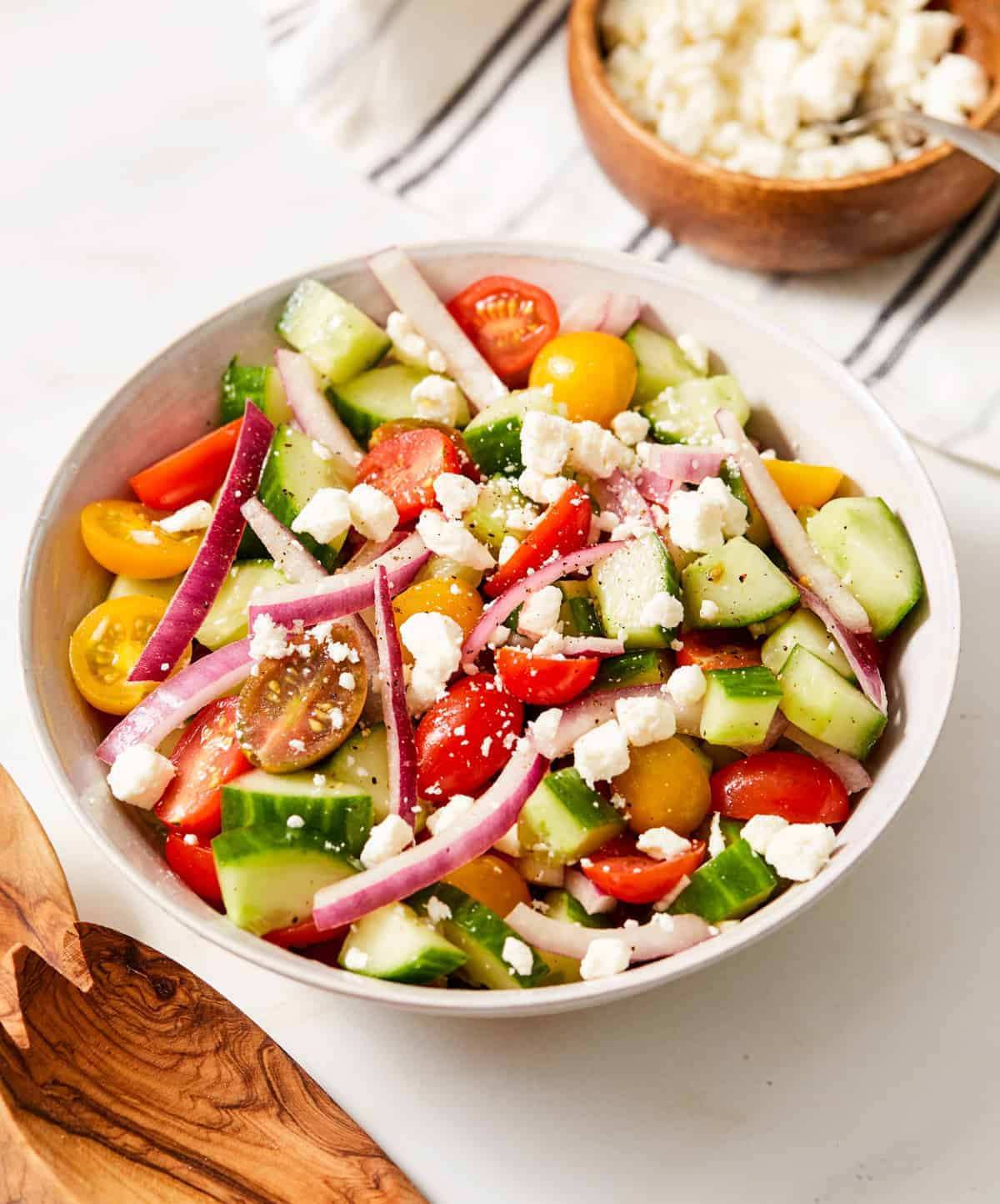 cucumber tomato and onion salad in a white bowl with feta cheese