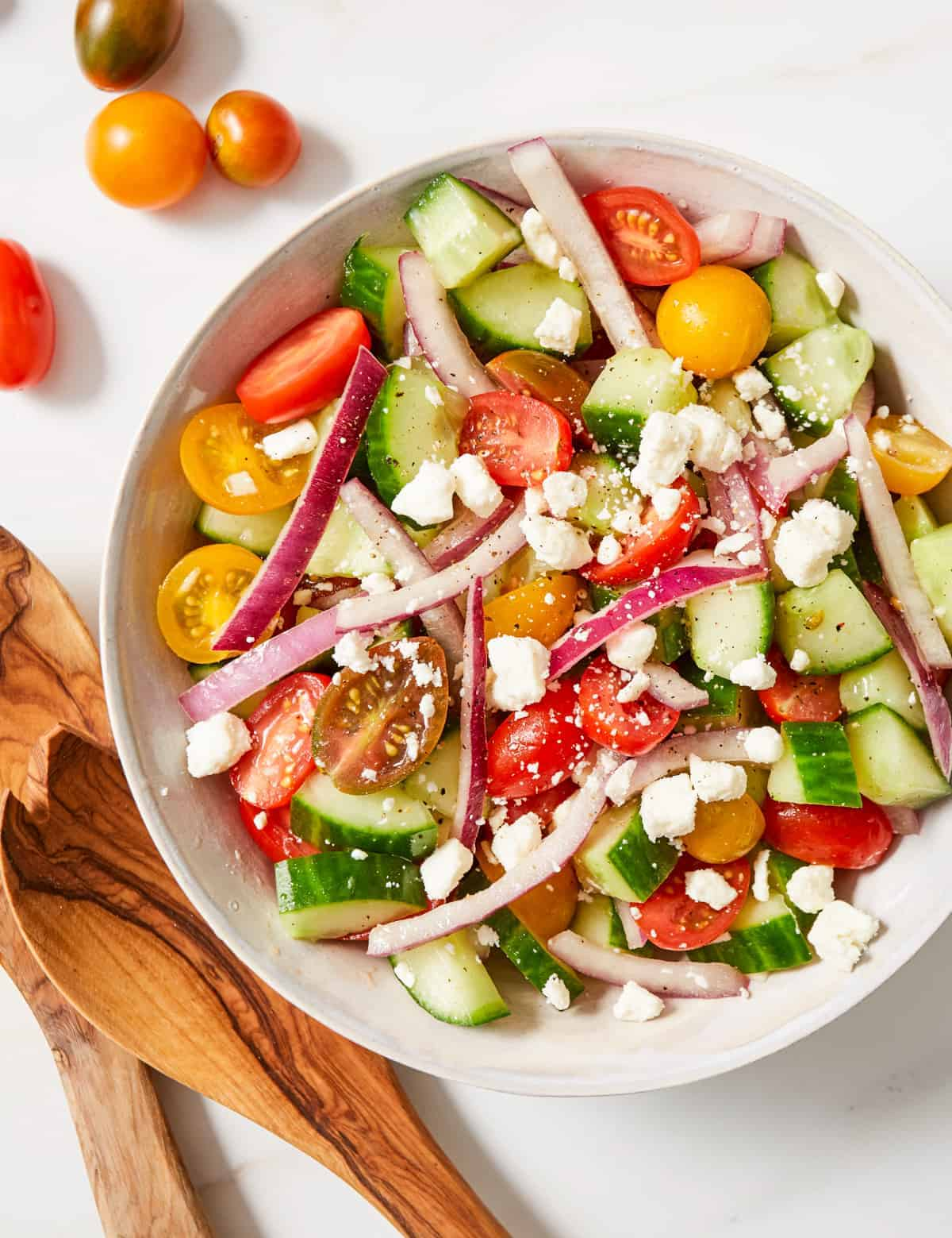 close up of cucumber tomato and onion salad topped with feta cheese