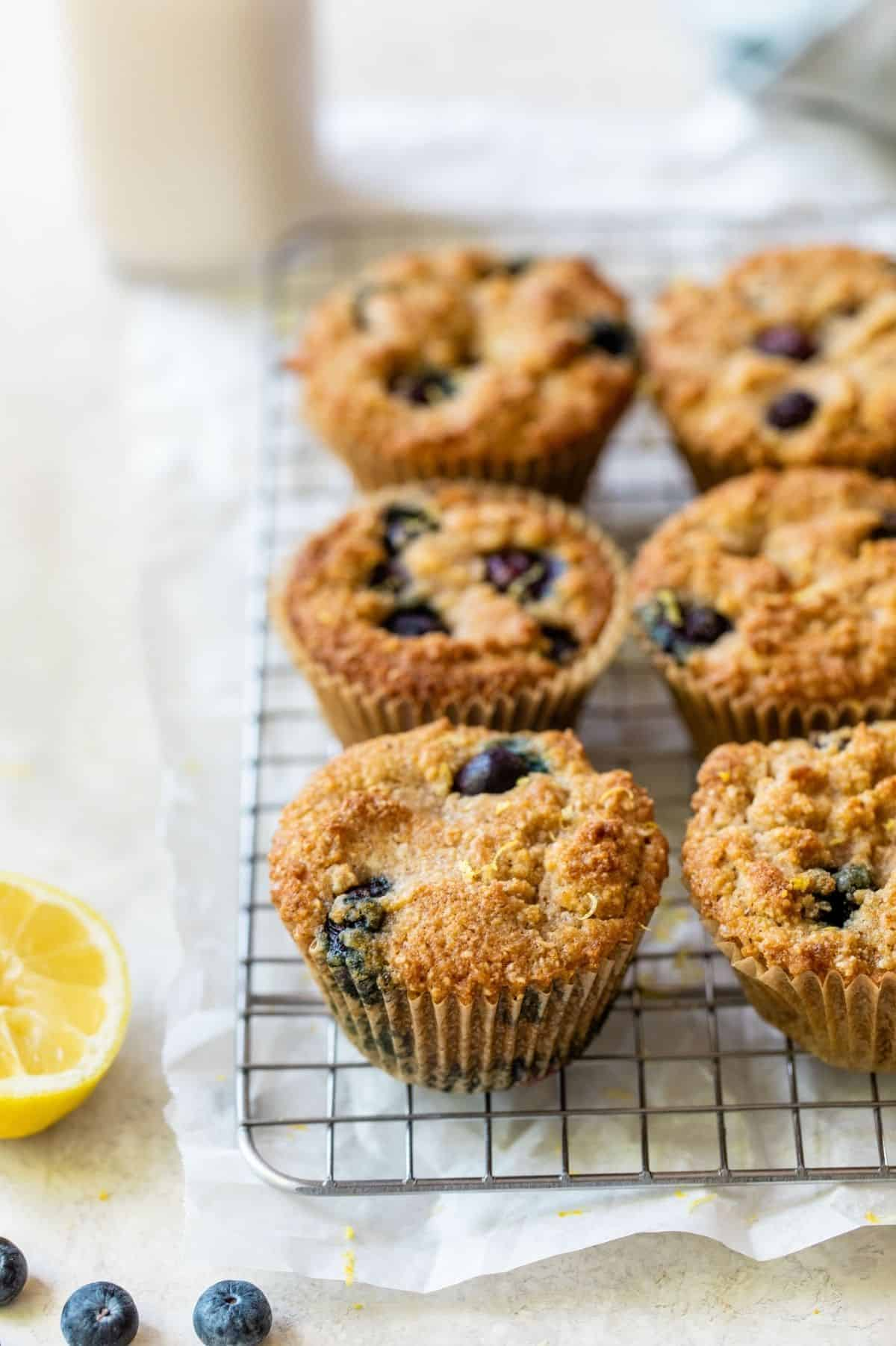 blueberry muffins on a cooling rack near a lemon