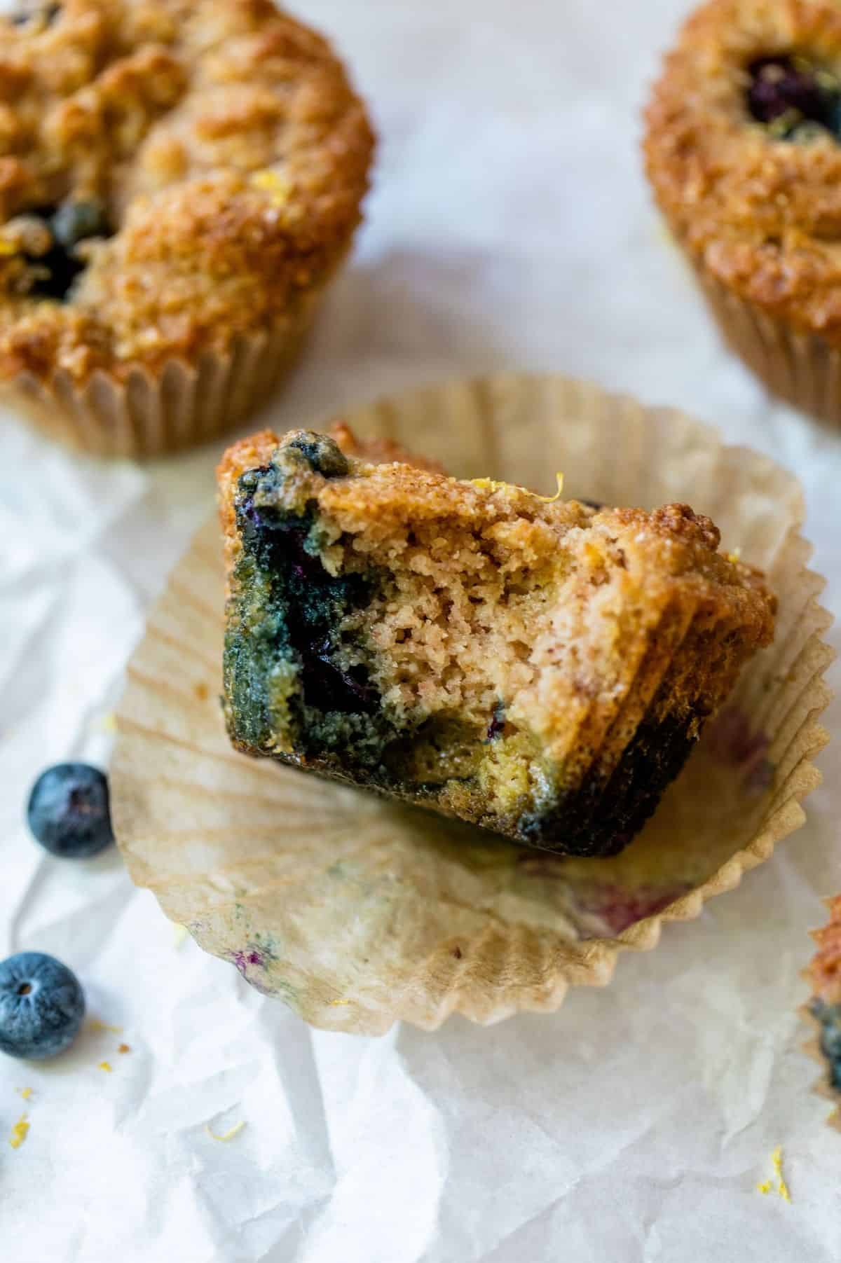 half eaten healthy blueberry muffin in a cupcake liner