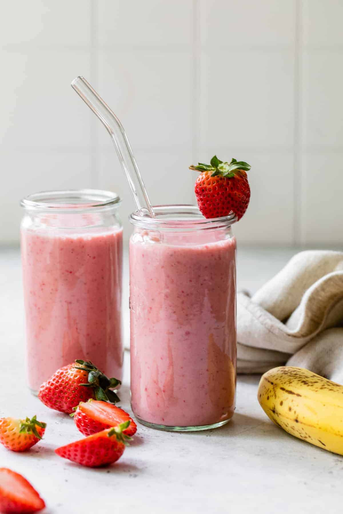 two banana strawberry smoothies side-by-side