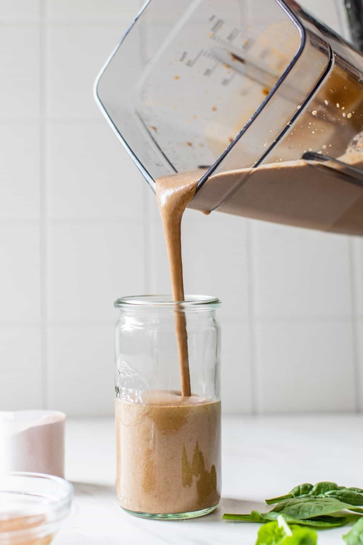 pouring a chocolate protein shake out of a blender and into a glass