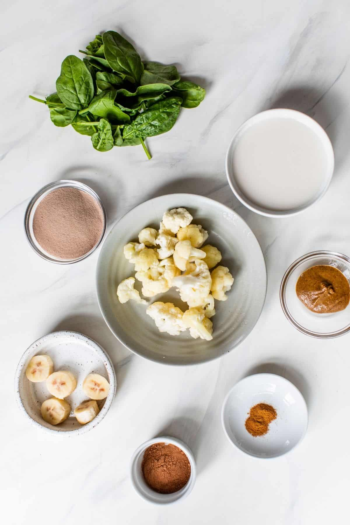ingredients for making a chocolate protein shake divided into little bowls