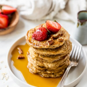 healthy oatmeal pancakes on white plate topped with strawberries