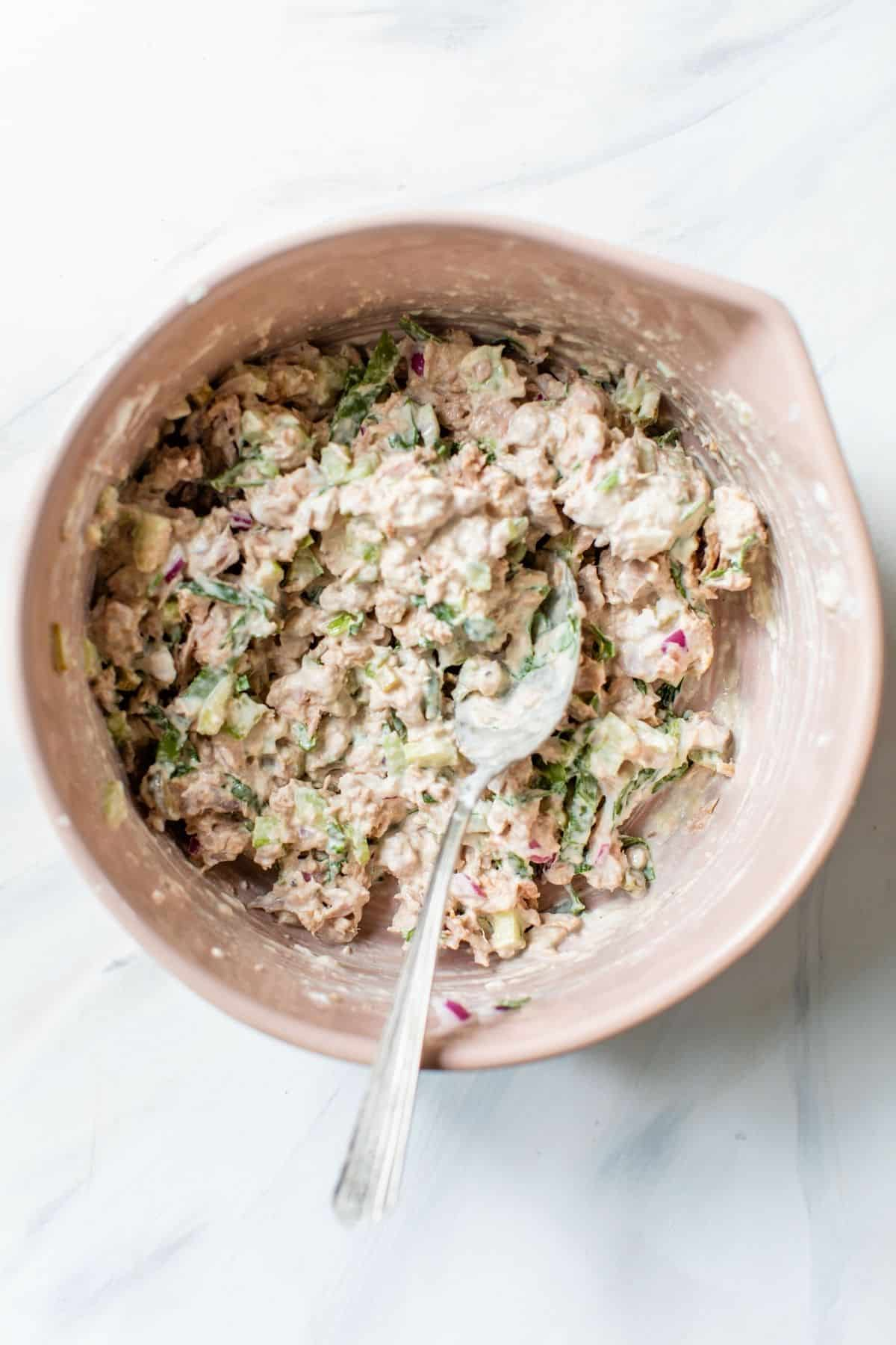 ingredients for tuna salad recipe stirred in a large mixing bowl